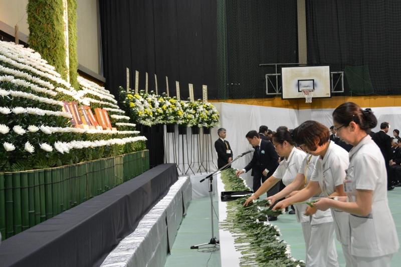 白菊を献花する教職員・学生